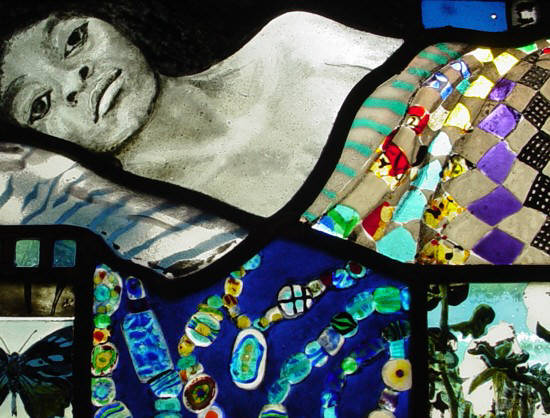 photgraphic detil of blues themed stained glss window shows woman under quilt and African trading beads